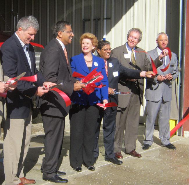 Anand Gangadharan (second to left) stands next to US Senator Debbie Stabenow at a ribbon cutting ceremony in November.