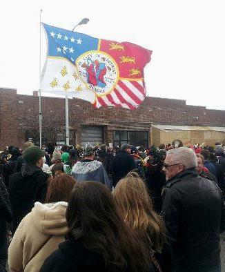 The Detroit flag flies at the Marche du Nain Rouge.