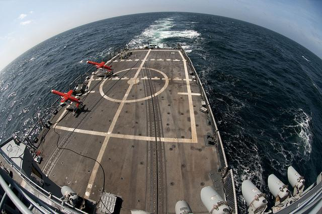 A pair of drones in launch position from the flight deck of the USS Underwood. This is a live-fire drone exercise in the Pacific Ocean.