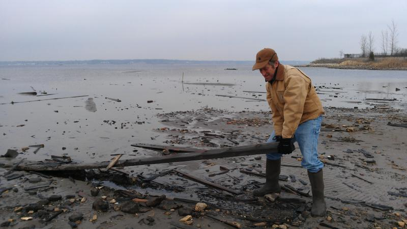 Terry Heatlie, a habitat restoration specialist, pulls a piece of slabwood out of the mud in Muskegon Lake.