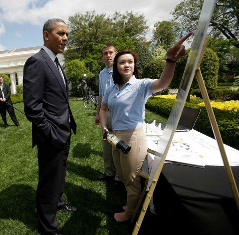 President Barack Obama listens to Spencer Ottarson, 19, center, and Julie Xu, 17, right, both from Williamston, Mich., as they explain their 'Offshore Rip Current Alert System (ORCA), Monday, April 22, 2013, during the White House Science Fair