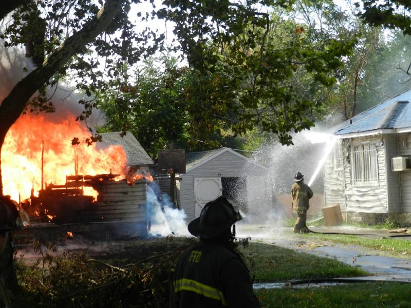 A Flint firefighter hoses down a home next to another building already consumed by fire.   Like many fires in Flint, the building that burned was vacant at the time.  (file photo)