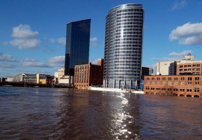 Many riverfront buildings have crews working to pump water out of basements (pictured Saturday).
