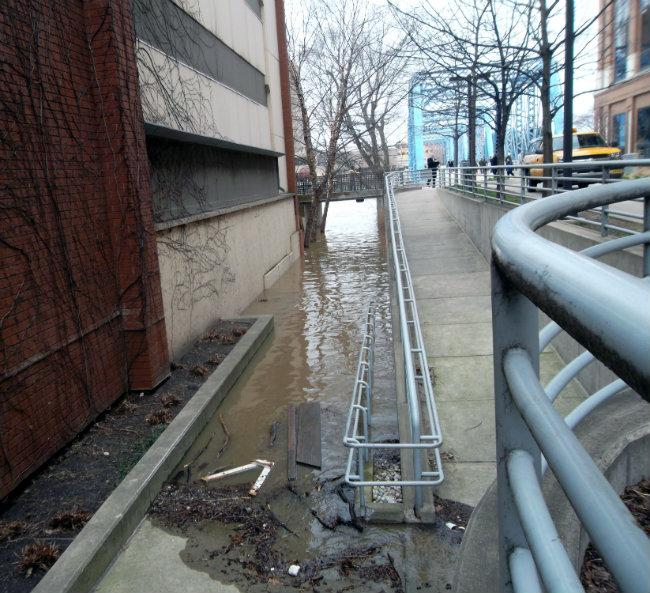 The Grand River inching up the sidewalk near the Courtyard Marriott Hotel (pictured Saturday).