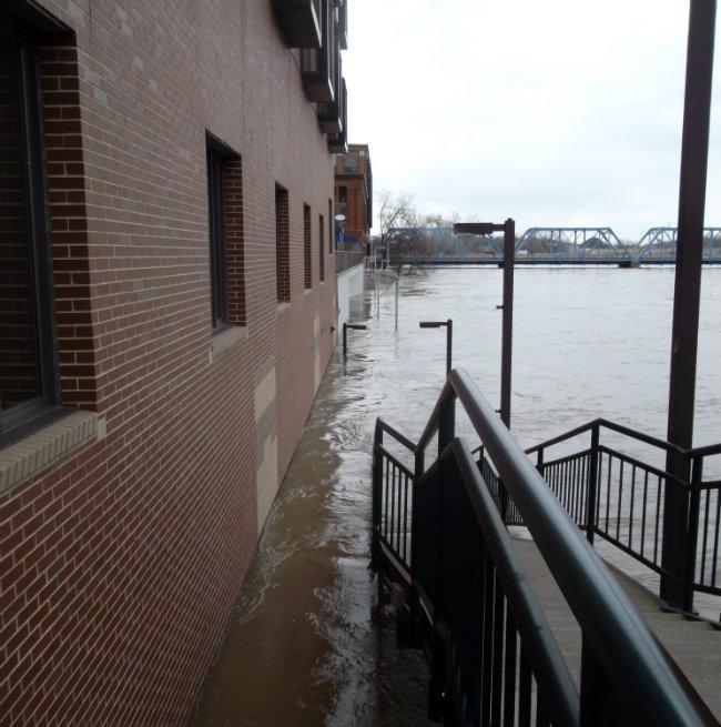 Water creeps up the side of an office building in Grand Rapids (pictured Saturday).