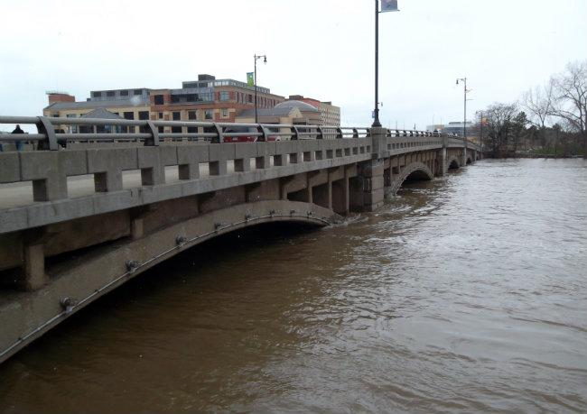 The Grand River nearly reaches the bottom of the Pearl Street bridge in downtown Grand Rapids (pictured Saturday).