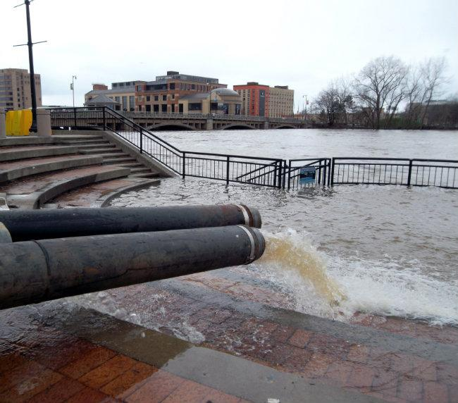 By Saturday afternoon the Amway Grand Plaza Hotel had three large pipes emptying water from the hotel's flooded basement into the Grand River.