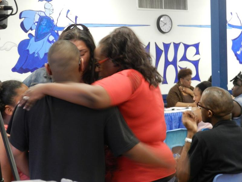 Parents and children embrace during a Buena Vista School Board meeting.