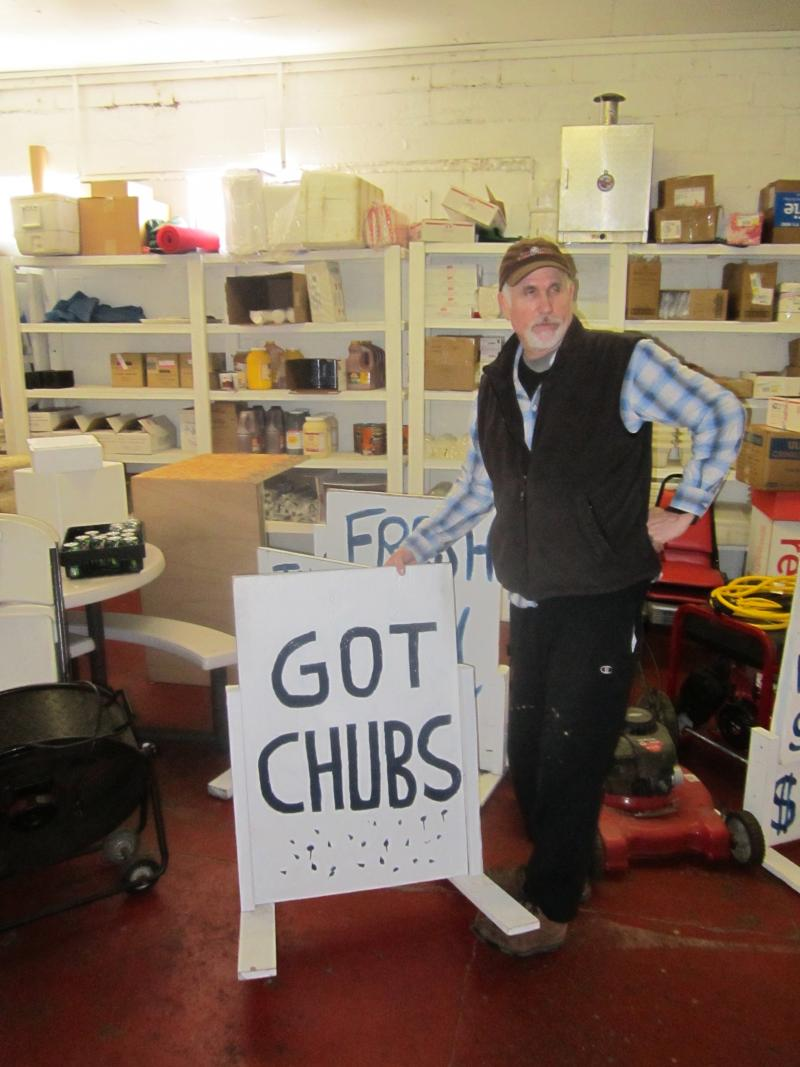 Mike Elwell at Port City Smokehouse in Frankfort, with the sign he puts out when he actually has chubs.