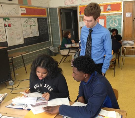 Patrick Tierney (standing) works with Cody High School students as part of U of M's Rounds Project.