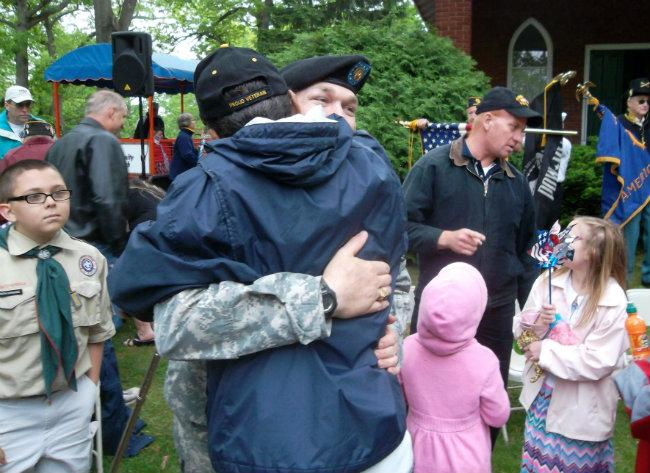 Specialist Jason Wright gets plenty of hugs and handshakes after the ceremony in Allegan on Memorial Day.
