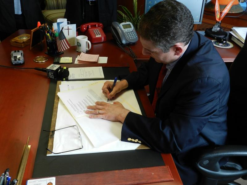 Lansing Mayor Virg Bernero signs his veto message on the FY2014 city budget