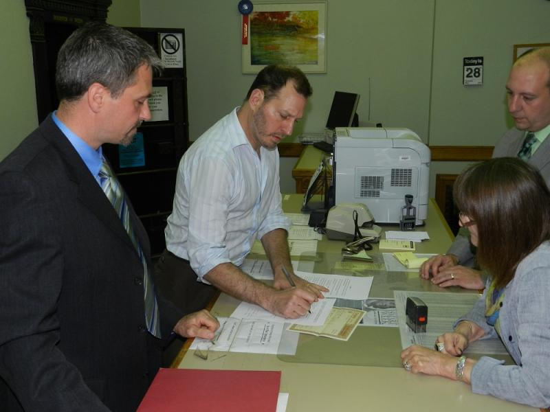 Lansing City Clerk Chris Swope (left) looks on as his husband Bradley Rakowski signs an affidavit in the Ingham County Register of Deeds office.  Register Curtis Hertel Jr. (right) looks on
