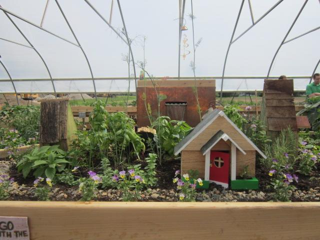 An herb and flower-filled fairy garden adds a touch of whimsy to the hoop house.