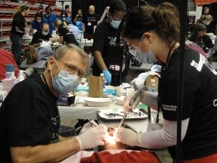 Volunteer dental professionals helping a patient at the Oklahoma Mission of Mercy event