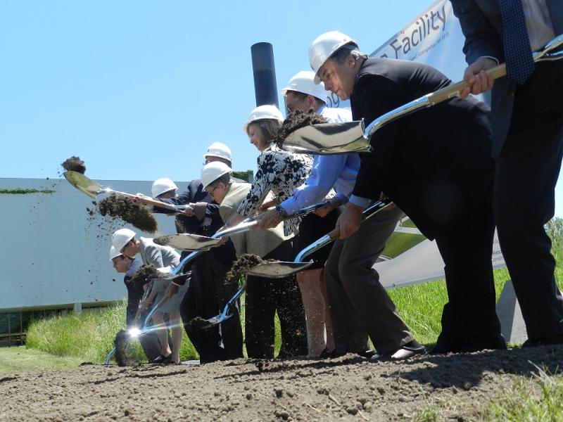 MSU administrators, trustees and others toss shovels full of dirt in the air during a ground breaking ceremony