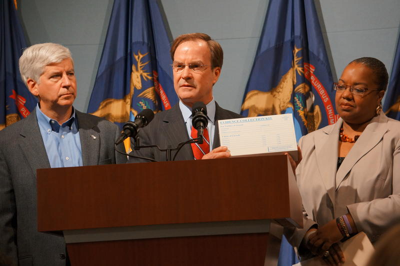 In 2013, Gov. Rick Snyder, Attorney General Bill Schuette, and Wayne County Prosecutor Kym Worthy held a news conference to announce $4 million to help reduce a backlog in processing thousands of rape kits. Schuette holds a rape kit box.