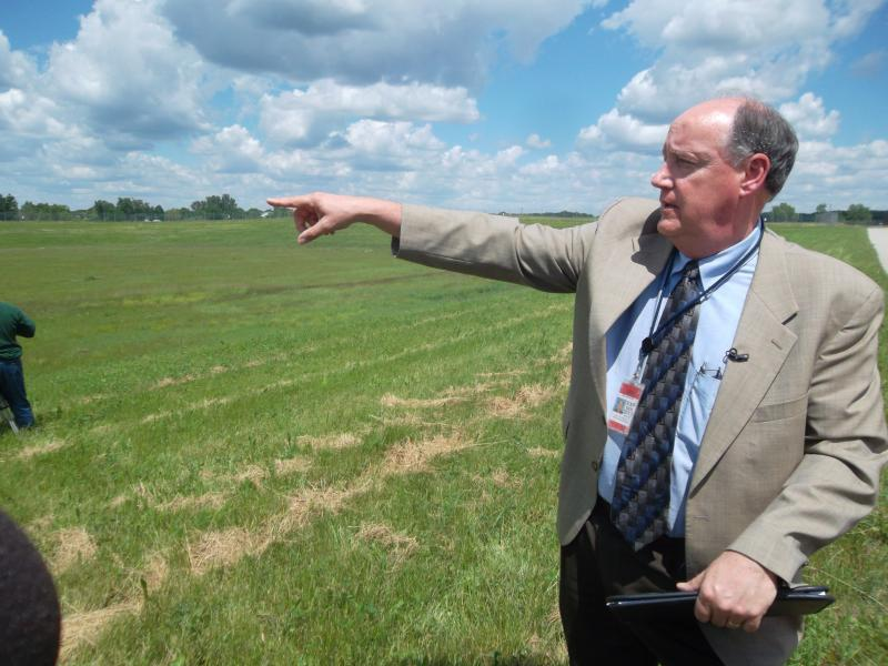 Gerald R. Ford International Airport's facilities director Tom Ecklund points out the current retention basin where the fluid mixes with storm water. It drains to what residents call Trout Creek. The basin is covered to discourage birds from congregating.