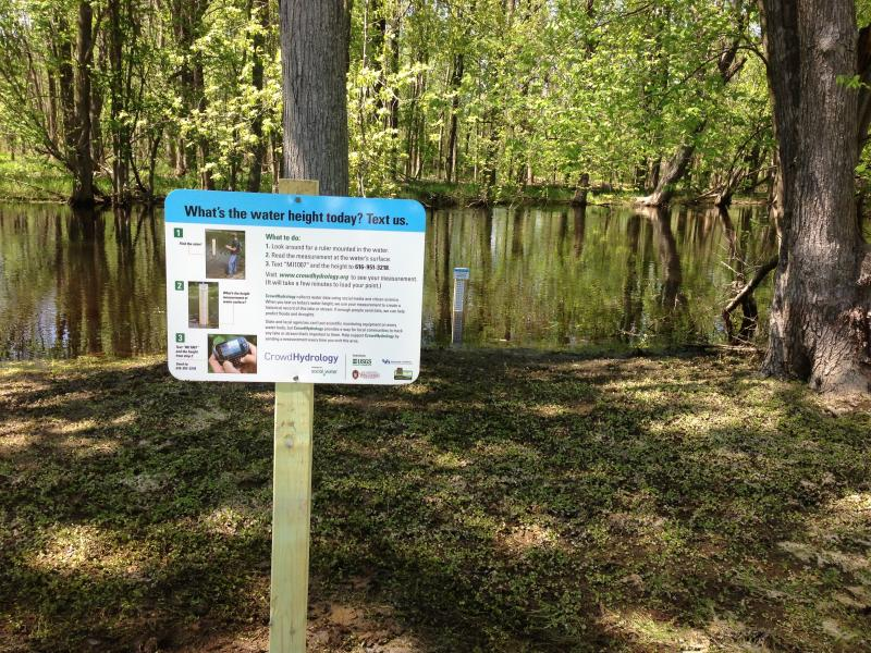 A CrowdHydrology site in Michigan. Each site includes a giant measuring staff and a sign explaining how passersby can contribute to the project by texting water levels to scientists.