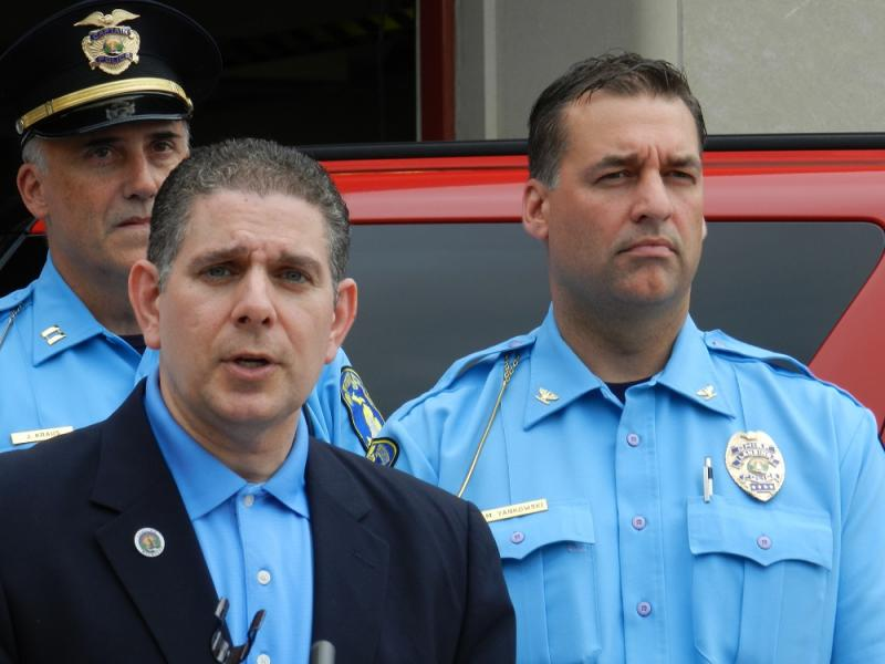 Interim Lansing Police Chief Mike Yankowski (right) listens as Mayor Virg Bernero speaks during a news conference on fireworks