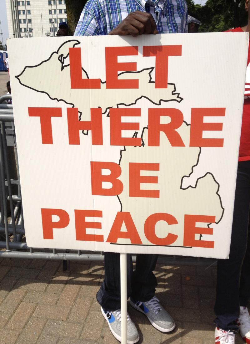 "A sign at the march reads ""let there be peace."""