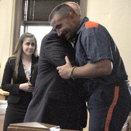 Victor Caminata hugs a member of his defense team.