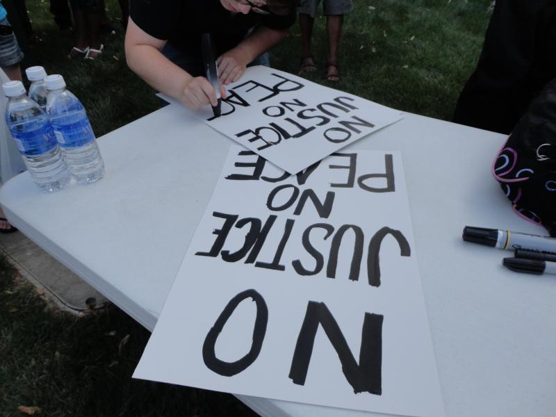 A protester making a sign with a popular cheer.