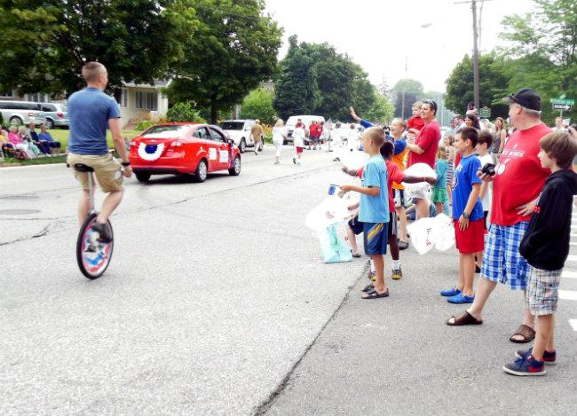 People watch the 79th annual Hollyhock Lane Independence Day parade in Grand Rapids.
