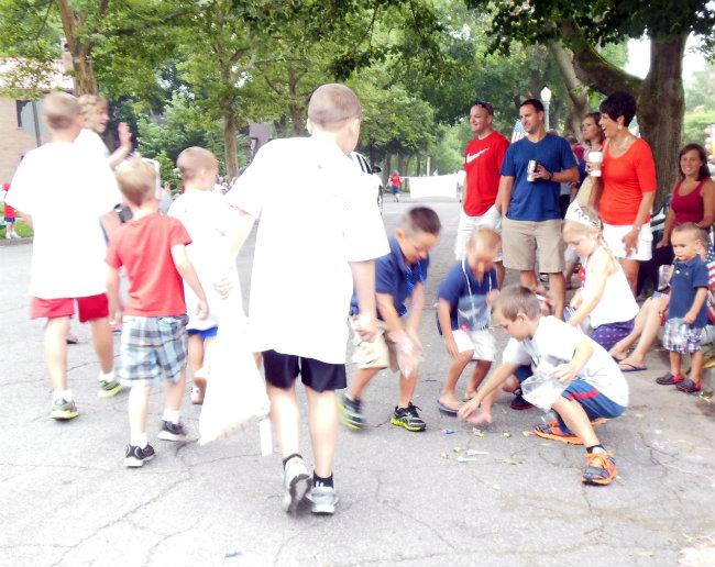 Kids snatch candy tossed at the Hollyhock Lane Independence Day parade in Grand Rapids.