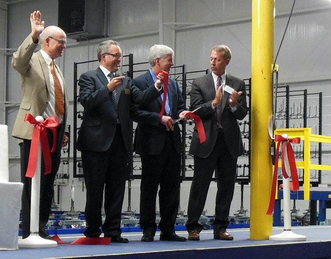 Governor Rick Snyder helps cut the ribbon on a new expansion of an auto supplier in Muskegon.