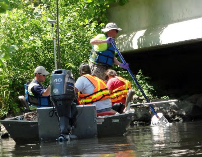 Workers on the Kalamazoo River performing poling operation to locate submerged oil.
