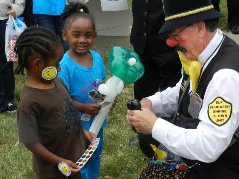 A clown makes balloon animals and flowers for two children at Flint's National Night Out event