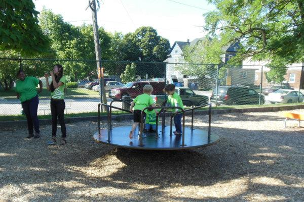 Kids play on a merry-go-round during a campaign kickoff in support of the parks millage.