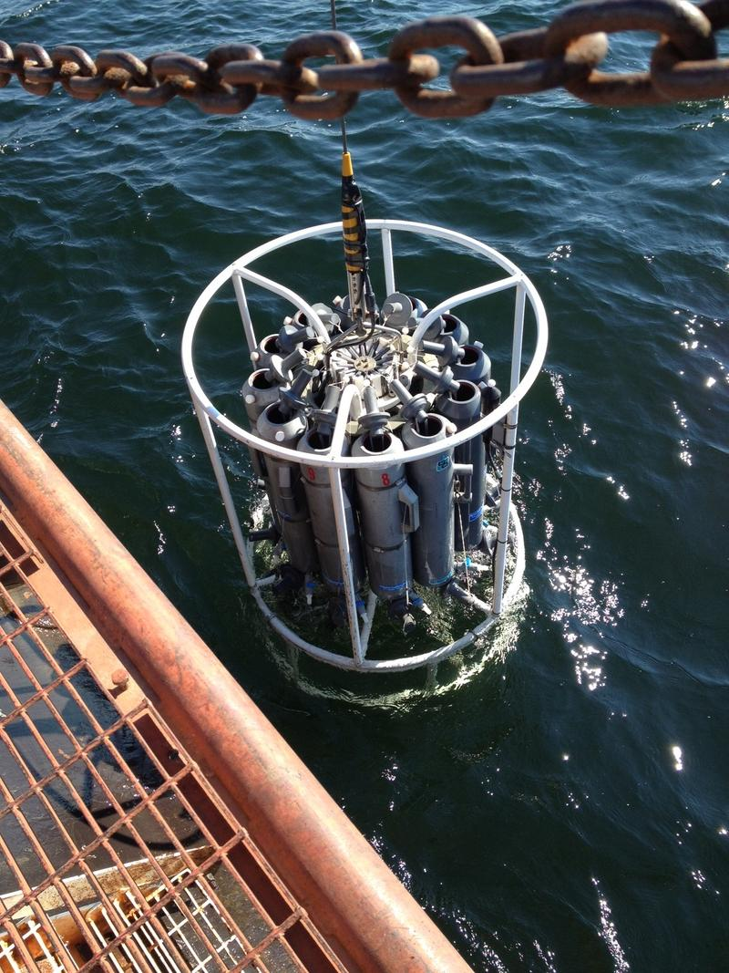 Researchers lower a scientific instrument into Lake Superior to measure the water's condition and temperature.