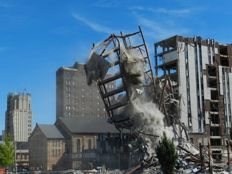 The tower of steel and concrete comes crashing to earth, missing First Congregational Church.