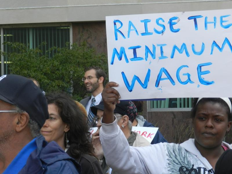 A woman holds a sign during a rally in Lansingon Wednesday on raising Michigan's minimum wage