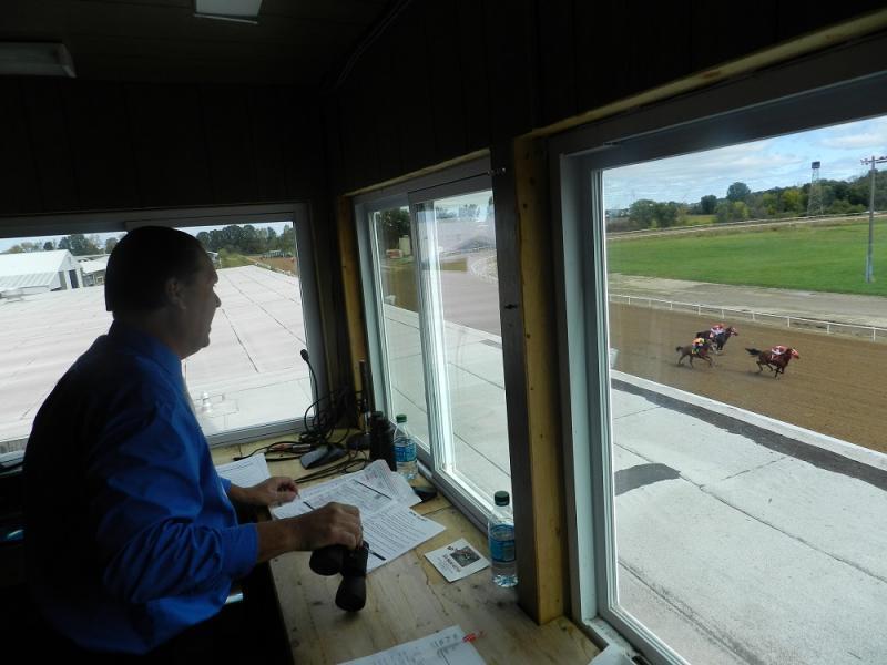 From his perch above the grandstand, announcer Scott Csernyik calls a quarter horse race at Mt. Pleasant Meadows