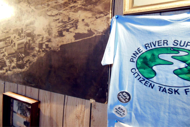 A Pine River Superfund Task Force t-shirt hangs next to an old photograph of the former chemical plant at the historic St. Louis depot station.