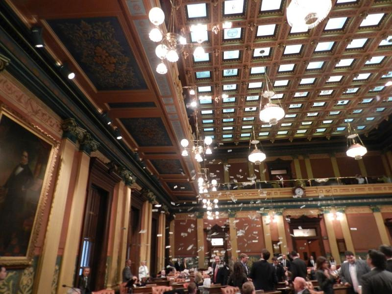 Anti-corruption protesters tossed fake million dollar bills off the state House gallery and onto Michigan lawmakers.
