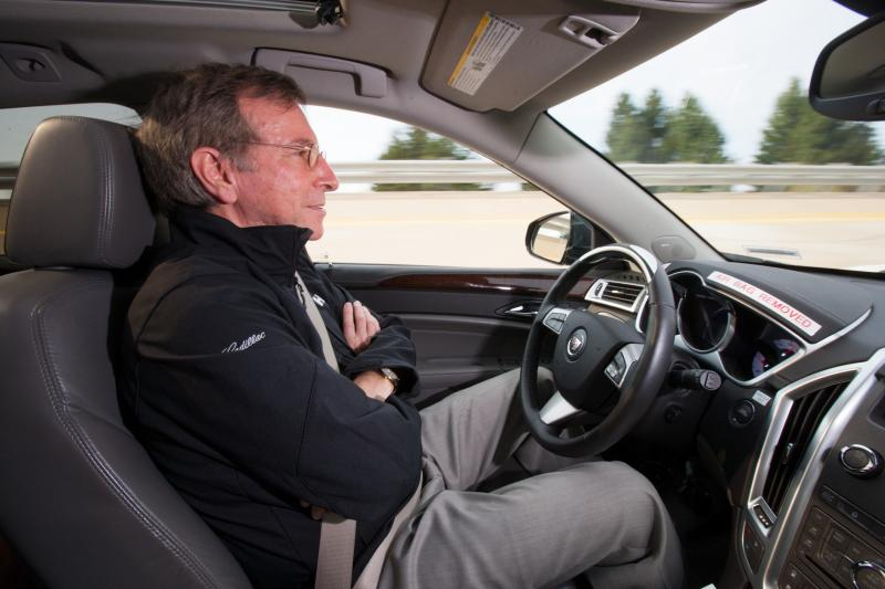 Jeremy Salinger sits with arms crossed as car drives itself