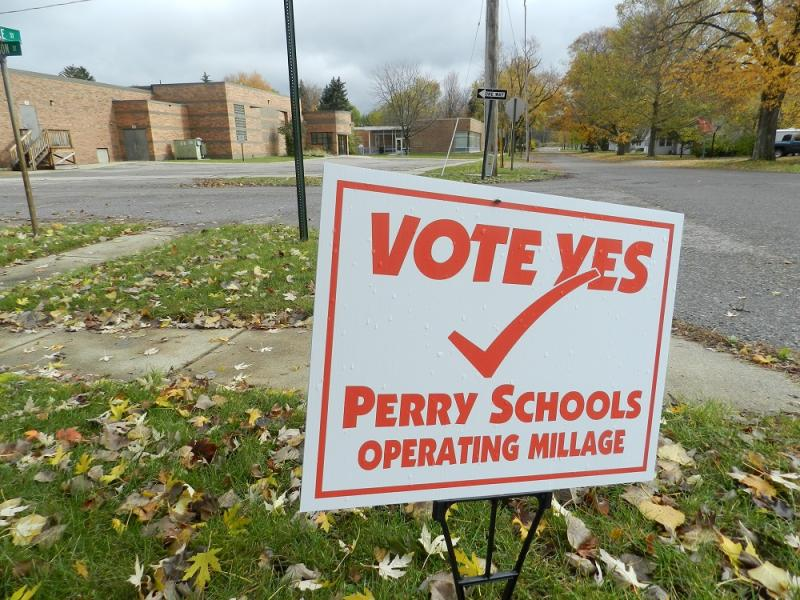 A pro-millage sign sits across the street from Perry East elementary school