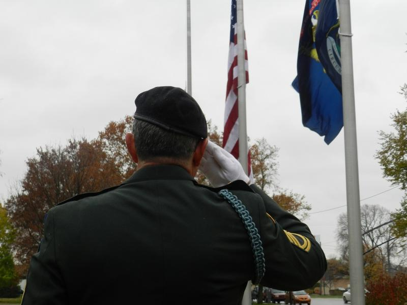 Retired Master Sergeant Tom Salvador salutes the flag during a Veterans Day ceremony at Flint city hall