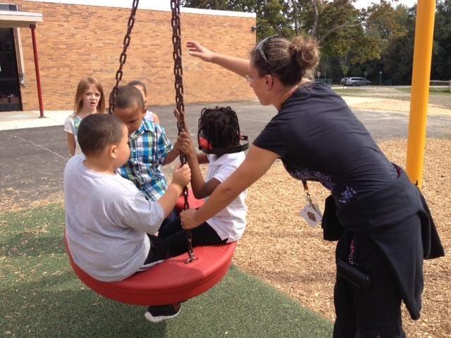 Djaba and Isaiah play on the tire swing while other kids wait in line.