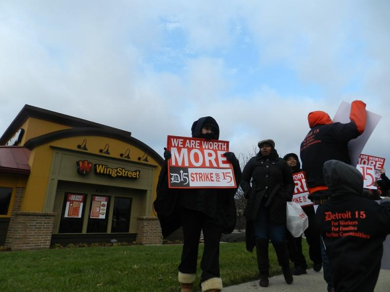 A small group pickets in front of a Pizza Hut on Lansing's south side