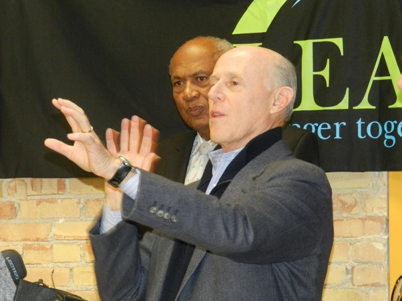 Co-developer Frank Kass gestures at a news conference.  Co-developer Joel Ferguson stands in the background.