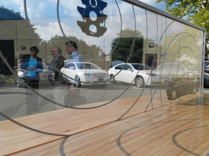 A glass panel display shows how vehicles equipped with the new technology will be able to communicate with one another and roadway infrastructure, like traffic signals at an August, 2012 Ann Arbor event on driverless cars.