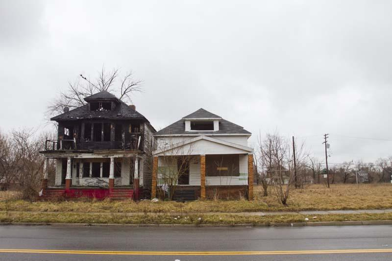 Two abandoned houses sit on a large vacant lot on Detroit's east side.