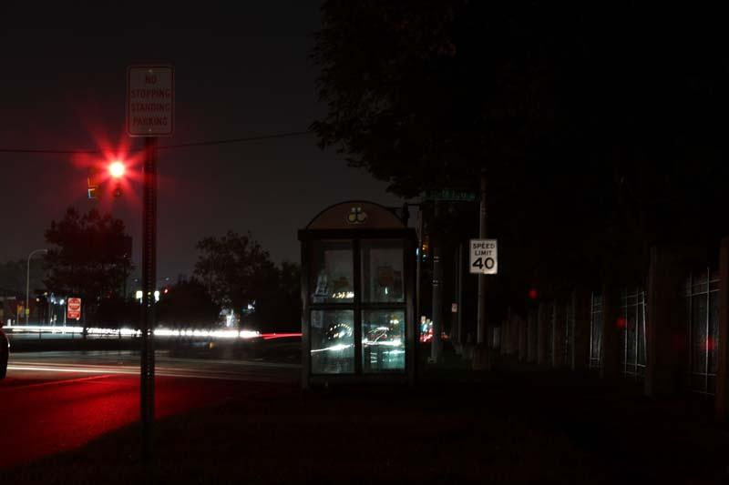 The only light at a bus stop comes from traffic signals and passing cars.