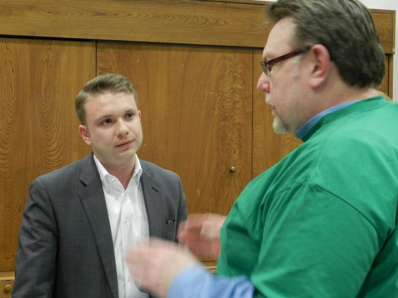 Lansing school board president Peter Spadafore (left) talks with Dan Hamilton with AFSCME 25