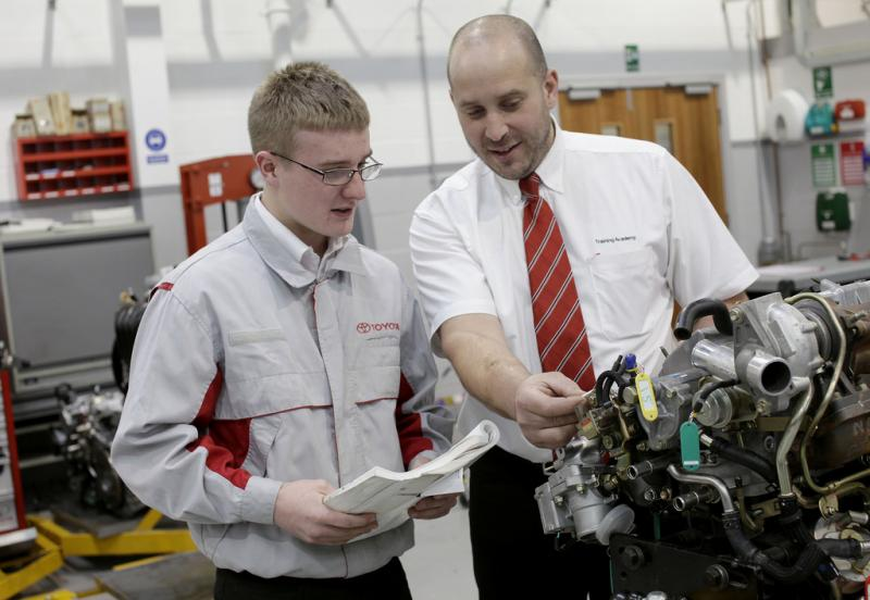 An engineer works with a student apprentice at Toyota.